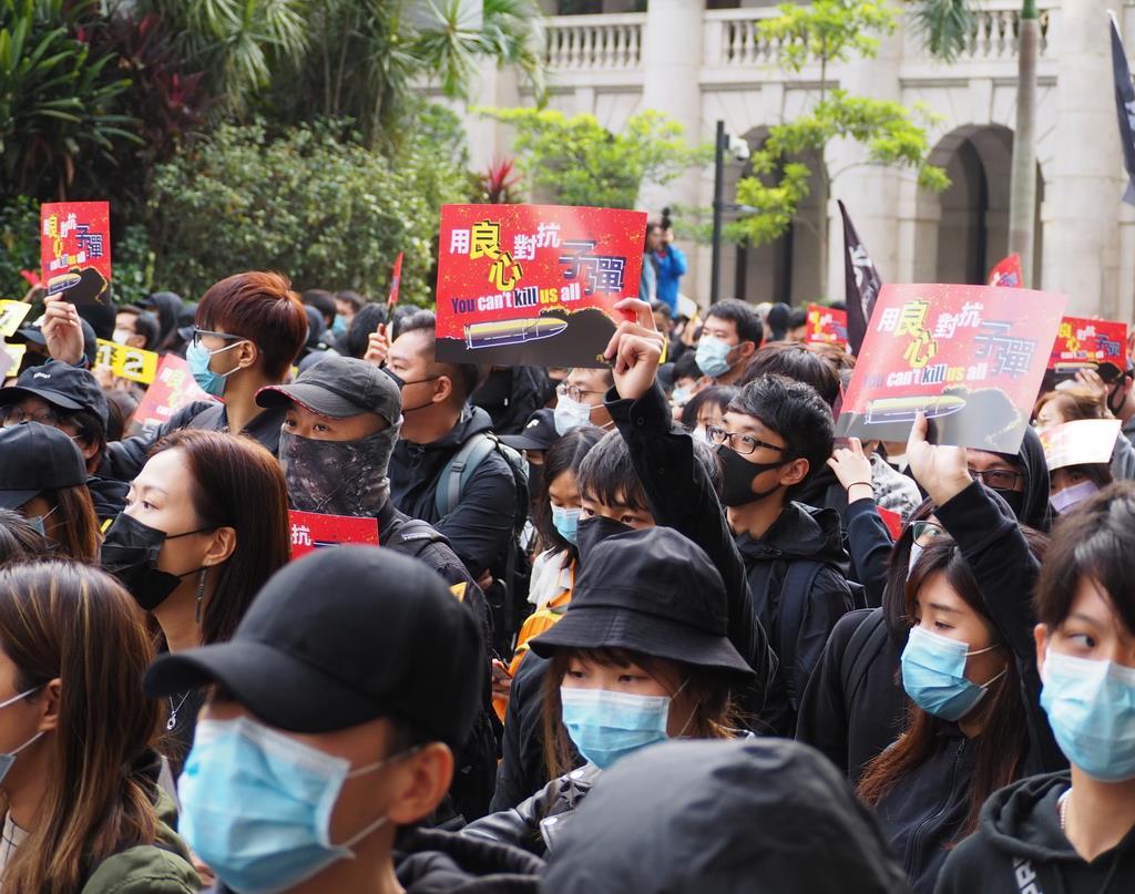19日、香港で行われた抗議集会。「良心で銃弾に対抗しよう」とのプラカードが掲げられた(藤本欣也撮影)