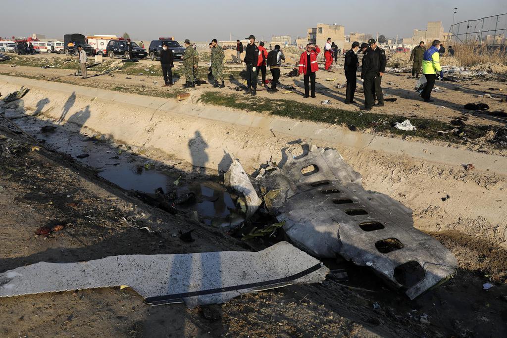 イラン・テヘランの空港離陸後に墜落したウクライナの旅客機の残骸と付近で活動する当局者ら=8日(AP)