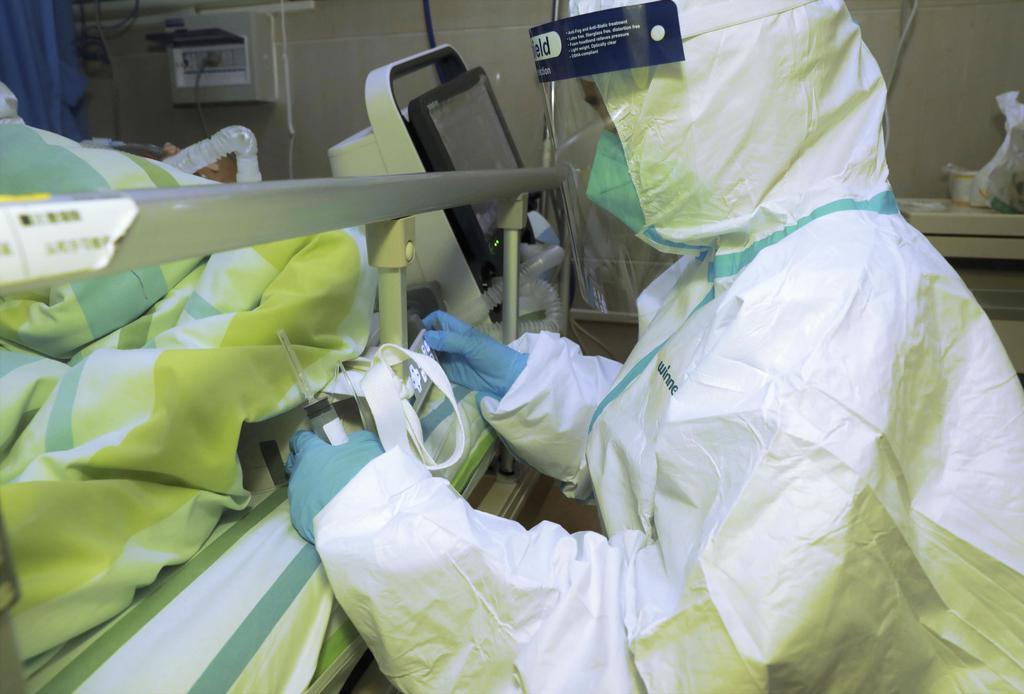 中国・武漢の病院で新型コロナウイルスによる肺炎の発症者の手当てをする医療関係者=22日(共同)