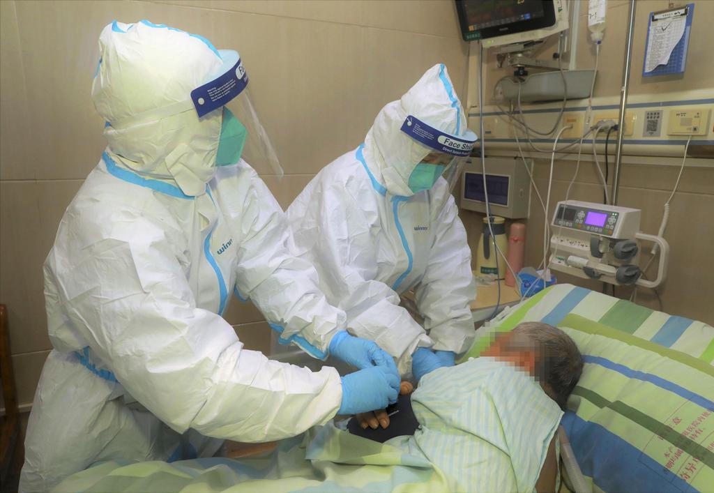 中国・武漢の病院で新型コロナウイルスによる肺炎の発症者の手当てをする医療関係者=22日(画像の一部をモザイク加工しています)(共同)