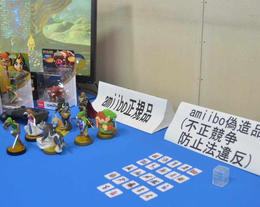 府警が押収した「アミーボ」の偽造カード(右)。正規品はフィギュアの形になっている=23日、府警本部
