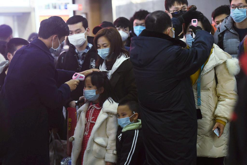 23日、中国・武漢から鉄道で浙江省杭州に到着した旅客の熱を測る職員ら(ロイター=共同)