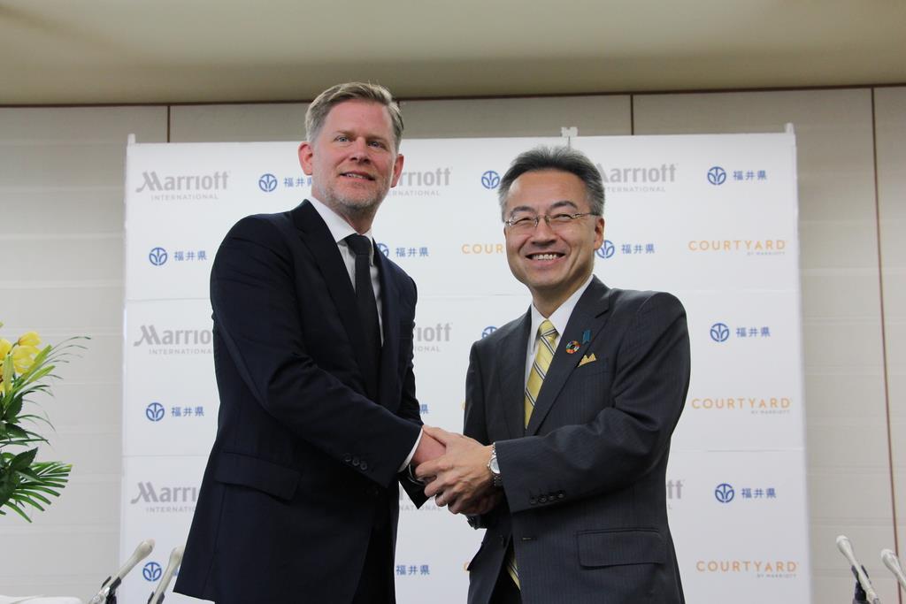 握手を交わすマリオット・インターナショナルのショーン・ヒル上席副社長(左)と福井県の杉本達治知事=福井県庁