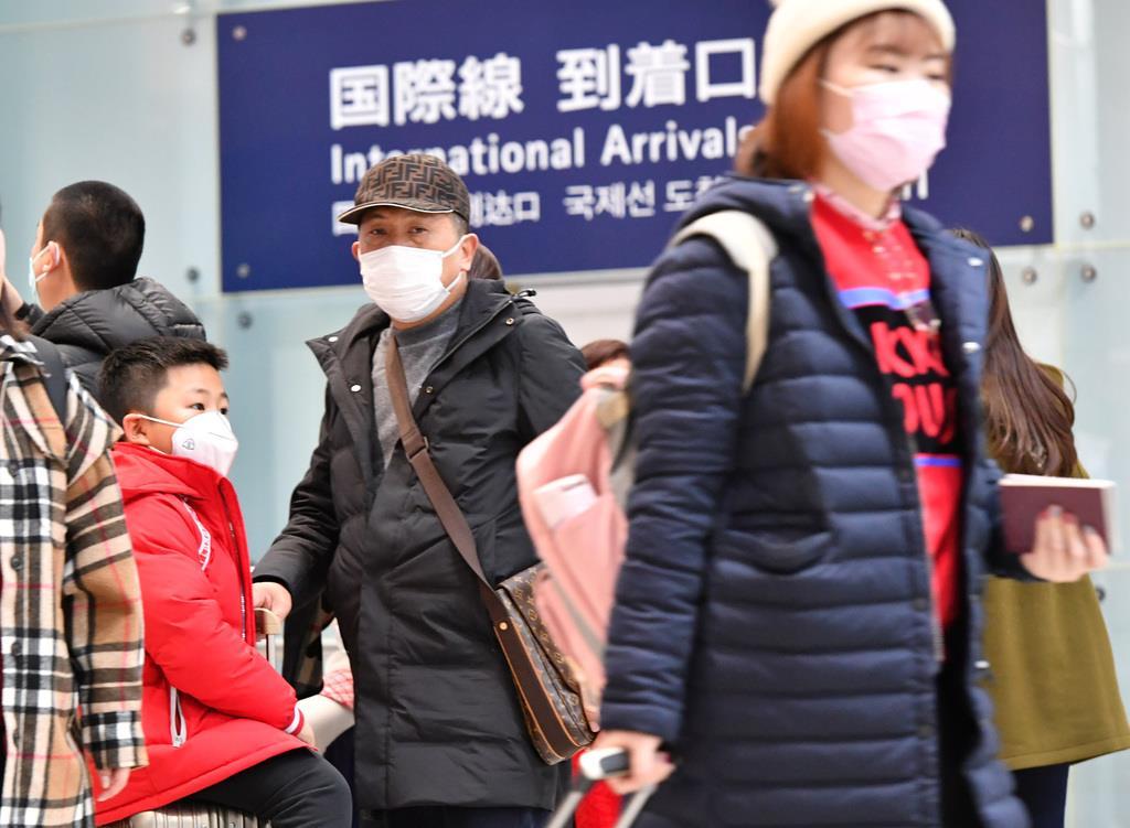 中国などから来た観光客で混雑する関西空港国際線到着口。中国で新型コロナウイルスによる肺炎が発生した影響で、マスクを着けた人の姿が目立つ=25日午後4時11分(沢野貴信撮影)