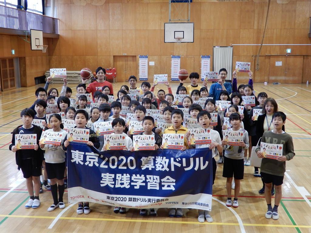 東京2020算数ドリルで実践学習した児童たちとバスケットボールを手に写真撮影する田中大貴(左奥)、安藤誓哉(右奥)=1月27日、三鷹市立羽沢小学校