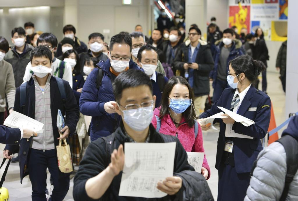 新型肺炎対策を強化した関西国際空港で「健康カード」を受け取る中国からの到着客ら=1月24日午後、関西国際空港