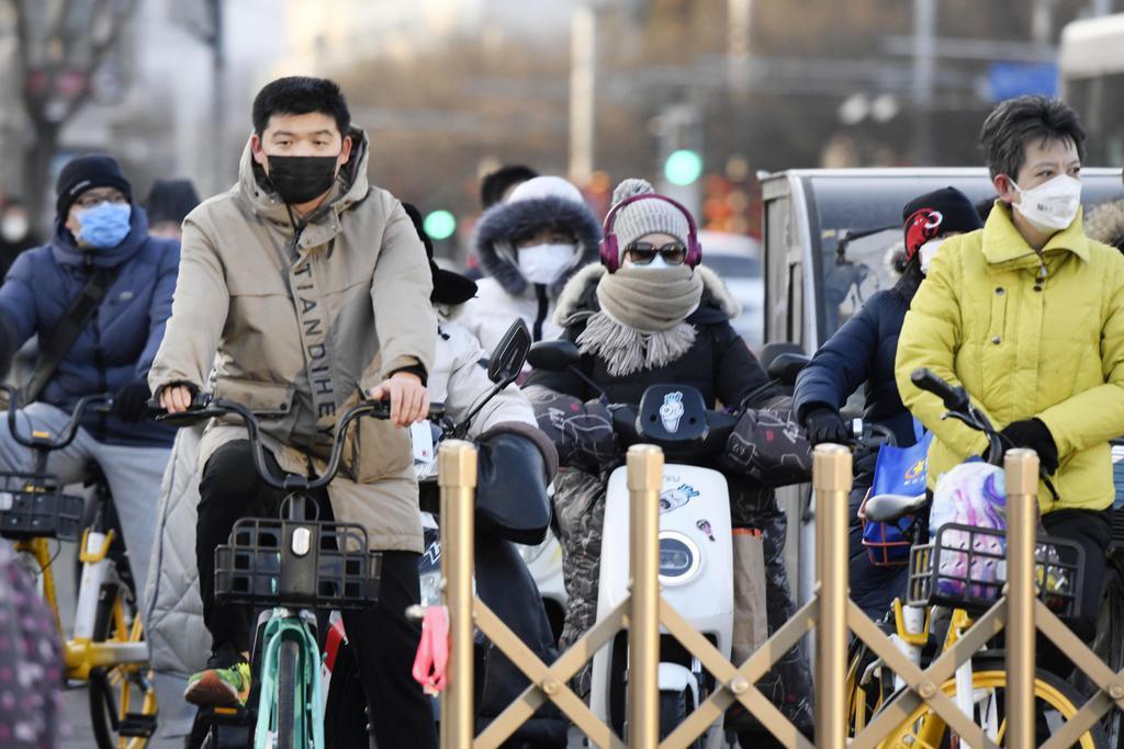 春節の大型連休が明け、マスク姿で行き交う北京市民ら=3日(共同)