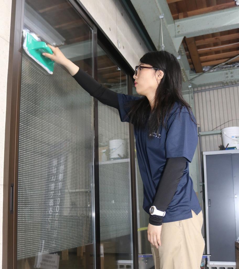 窓ガラスのコーティング作業をするジルベルトの利用者=神戸市須磨区