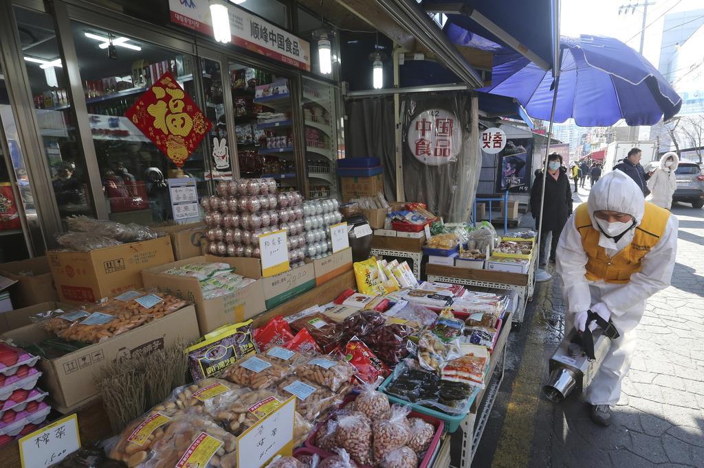 新型コロナウイルスの拡大防止措置として、韓国・ソウルの中華街の中国食材店前で消毒剤をまく防護服姿の作業員=2020年2月5日(AP)