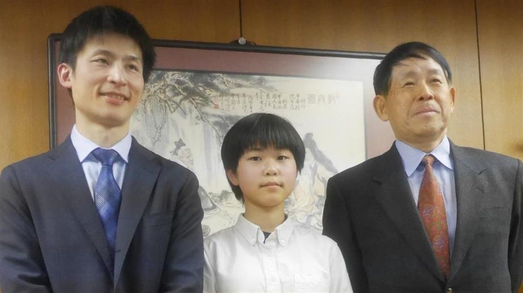プロ入りを決めた張心澄さん(中央)。父の張栩九段(左)と祖父の小林光一名誉棋聖に祝福された