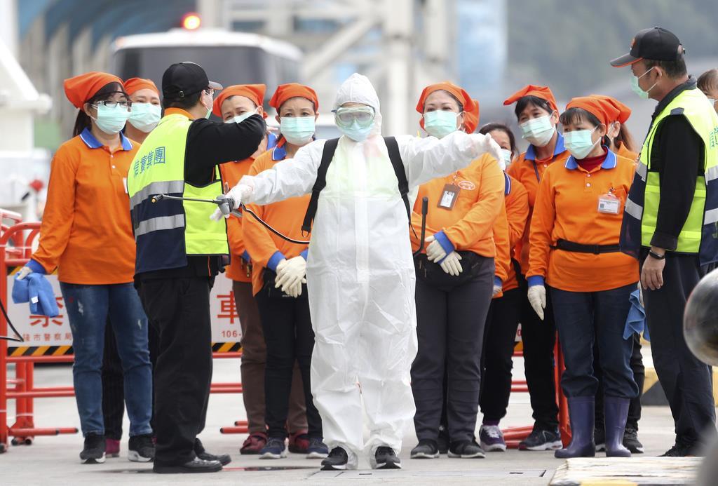 基隆港に停泊しているクルーズ船に乗るために待機する防護服を着た防疫作業員ら=2日、台湾(AP)