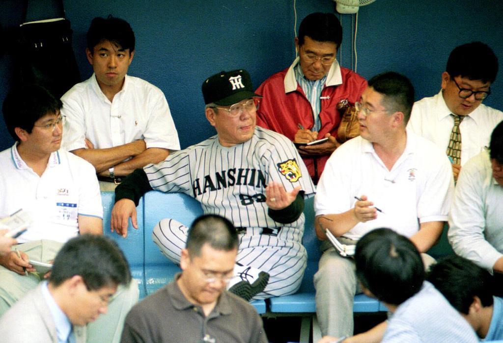 雨天中止となり、ベンチで記者団に囲まれ2時間も話した阪神・野村克也監督(中央)=平成11年6月22日