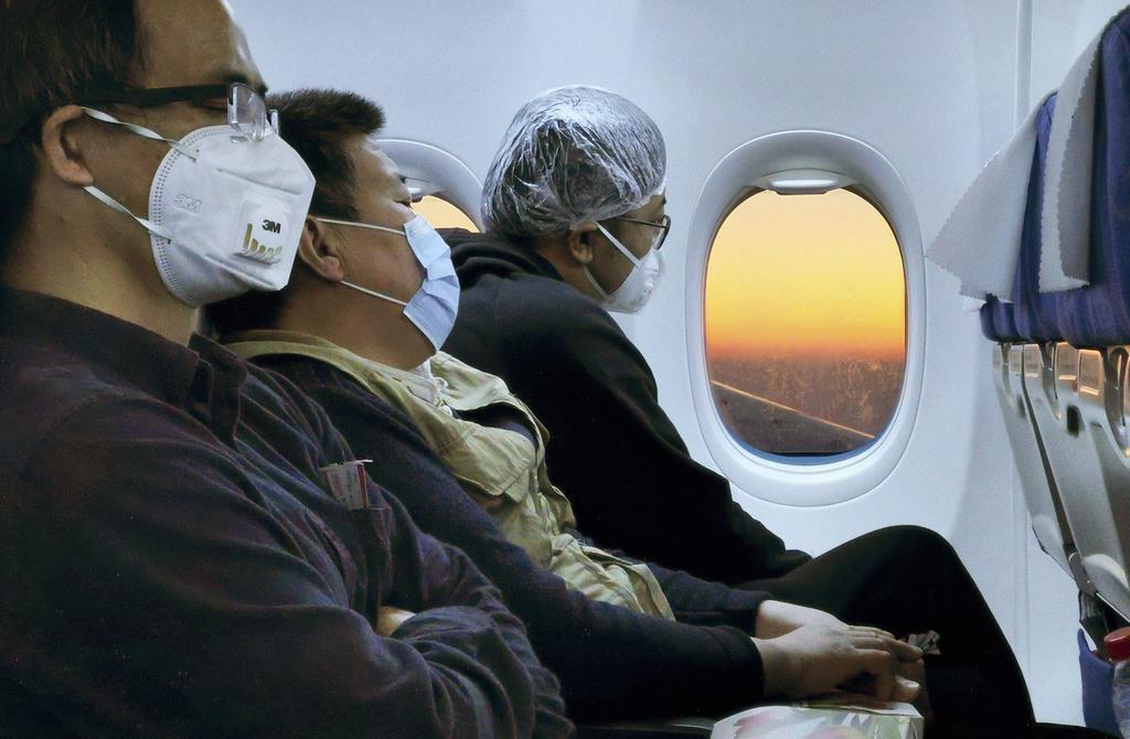中国海南省から北京へ向かう航空機内でマスクを着用する乗客=10日(共同)