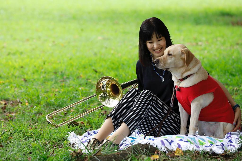榎並悦子さんが撮影した、トロンボーンソリスト・鈴木加奈子さんと、パートナーの盲導犬「アリエル」の一枚