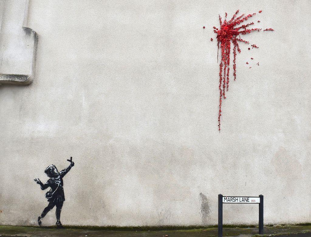 13日朝、英南西部のブリストルで見つかった少女や赤い花をあしらった作品(ロイター)