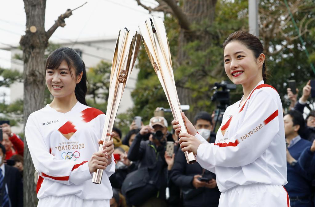 聖火リレーのリハーサルで、トーチを手にポーズをとる女優の石原さとみさん(右)ら=15日午前、東京都羽村市