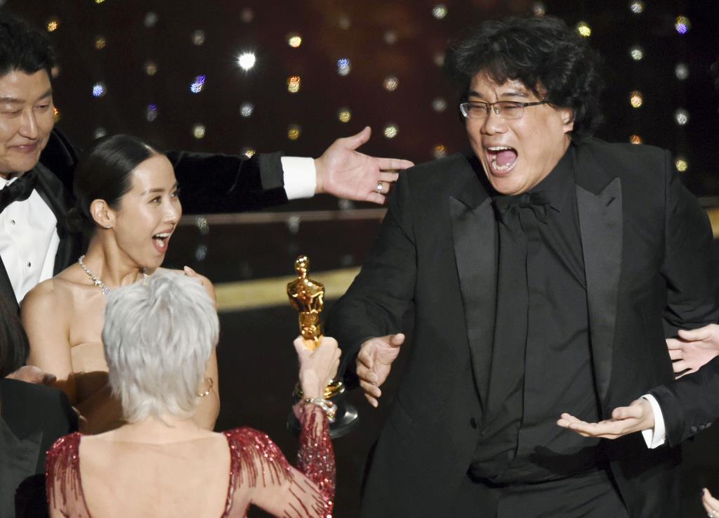 第92回米アカデミー賞で作品賞を受賞し、喜ぶ「パラサイト」のポン・ジュノ監督(右)と出演者ら=9日、米ハリウッド(AP=共同)