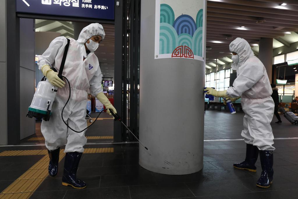 1月24日、韓国・ソウルの鉄道駅で消毒剤をまく作業員ら(ゲッティ=共同)