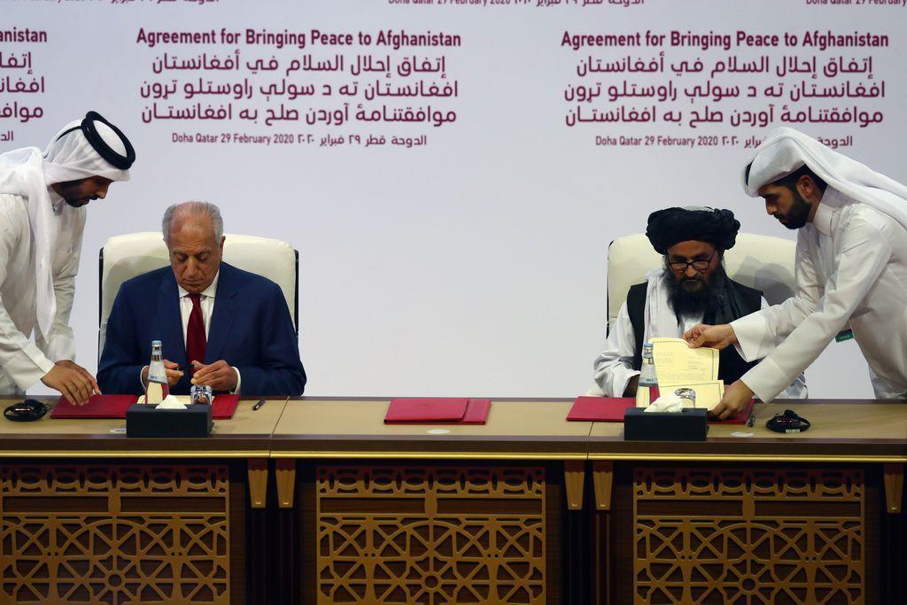 29日、合意文書に署名するタリバンのバラダル幹部(右)とハリルザド米特使=カタール・ドーハ(ロイター)