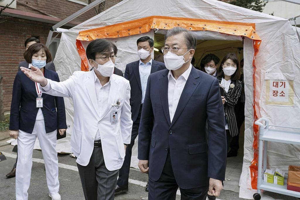 新型コロナウイルスの感染者を治療中の病院を視察する韓国の文在寅大統領(手前右)=1月28日、ソウル(大統領府提供・共同)