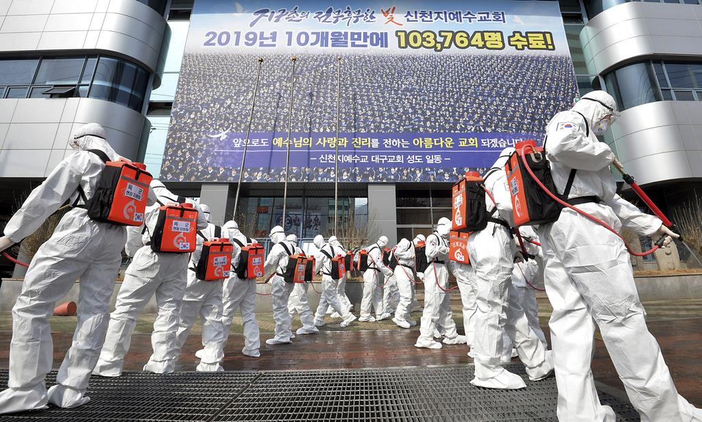 韓国南東部大邱の新天地イエス教会施設前で、防護服を着用して消毒剤を散布する兵士ら=1日(AP)
