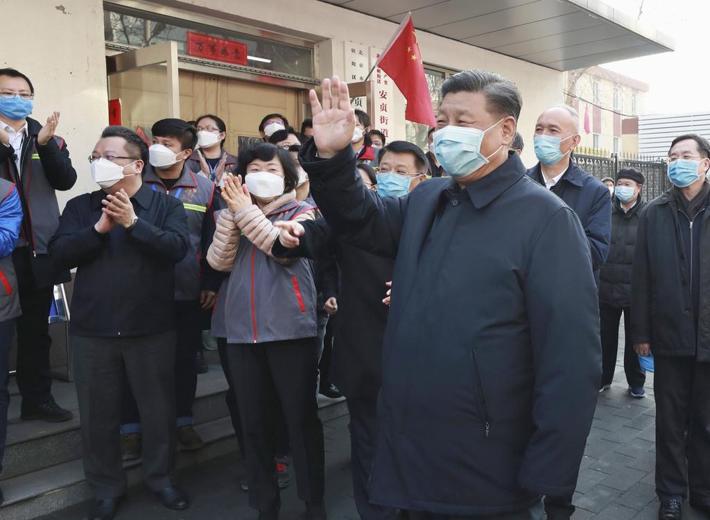 2月10日、北京市内の施設を視察し、マスク姿で手を振る中国の習近平国家主席(右手前)(新華社=共同)