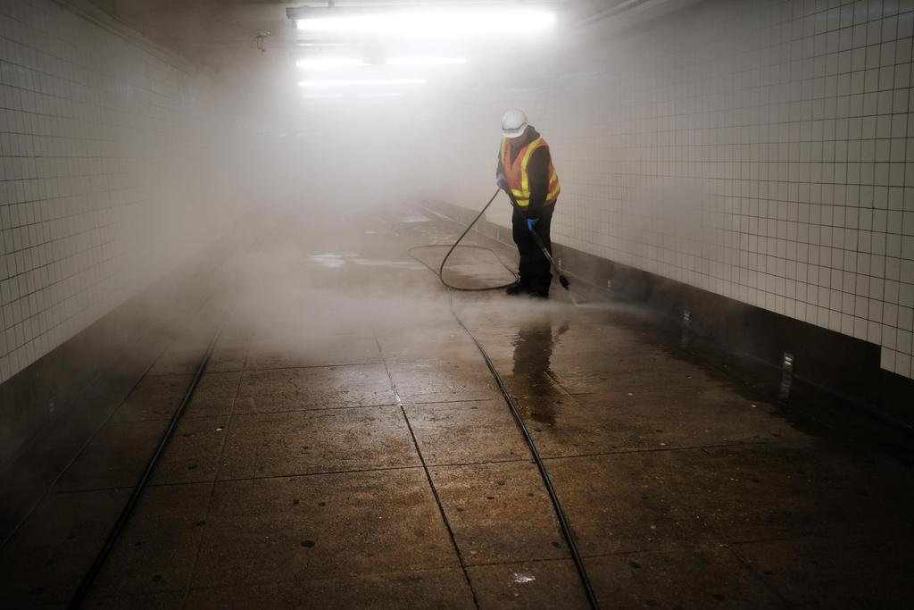 11日、米ニューヨークの地下鉄で、新型コロナウイルス対策として消毒作業をする清掃員(ゲッティ=共同)