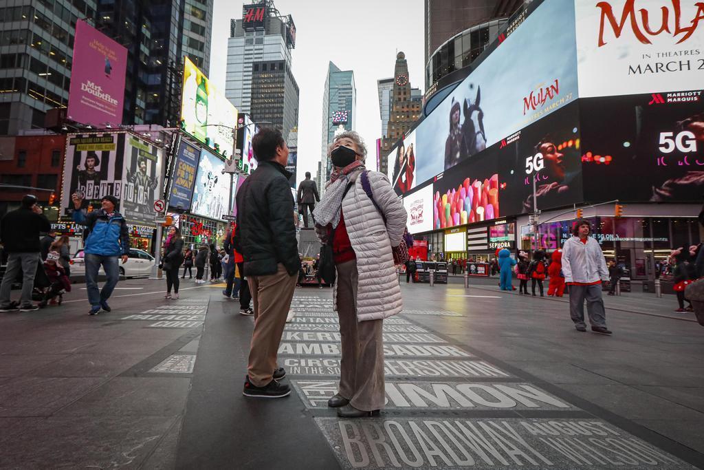 12日、米ニューヨーク中心部の繁華街タイムズスクエアでマスクを着けて歩く人(AP)