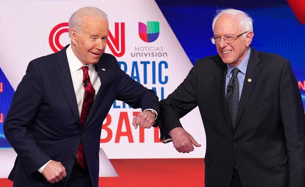 15日、民主党候補者討論の前、感染を防ぐため握手の代わりにひじをつき合うバイデン前副大統領(左)とサンダース上院議員=ワシントン(ロイター)