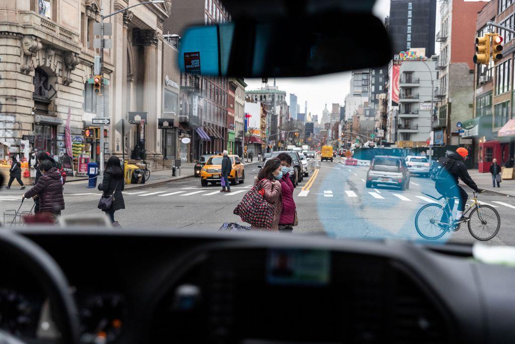 ニューヨークの街中でマスクを着用して歩く人たち=17日(ロイター)