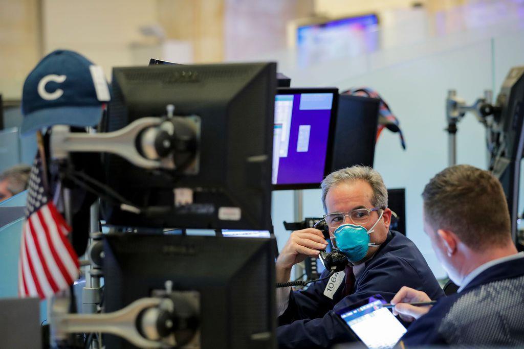 マスクを着用して業務にあたるトレーダー=19日、ニューヨーク証券取引所(ロイター)