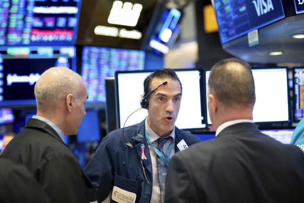 証券取引所で働くディーラー=20日、ニューヨーク(AP)