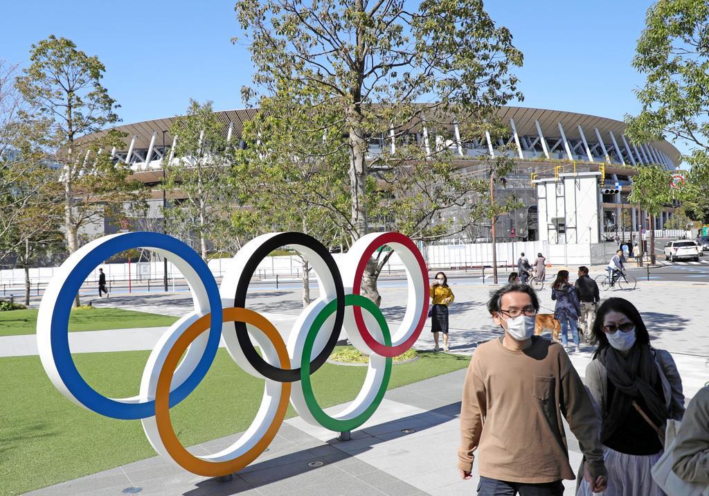 新国立競技場の前をマスク姿で歩く人たち=東京都新宿区(撮影・桐原正道)