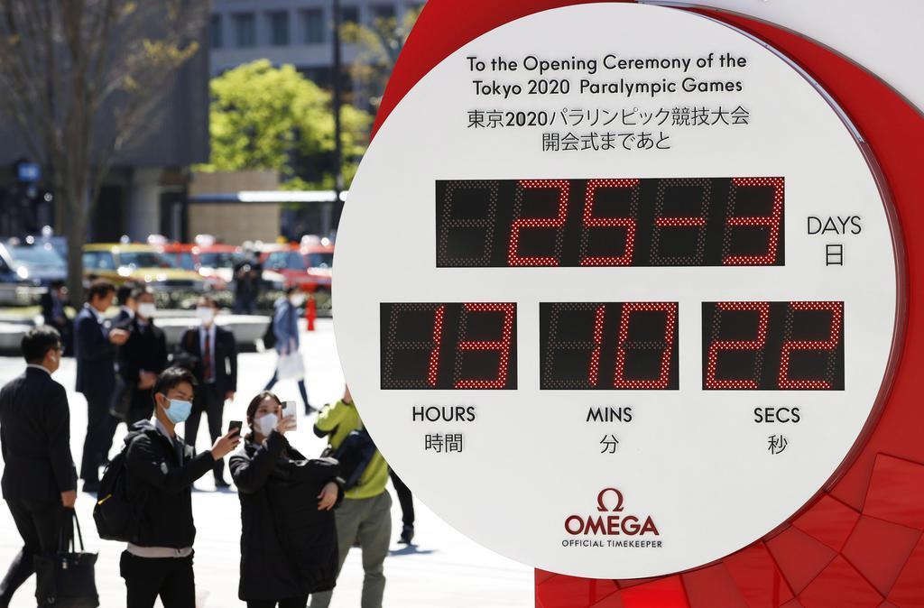 東京五輪・パラリンピックの延期が決まり、現在日時の表示に変更されたJR東京駅前のカウントダウン時計=25日午後
