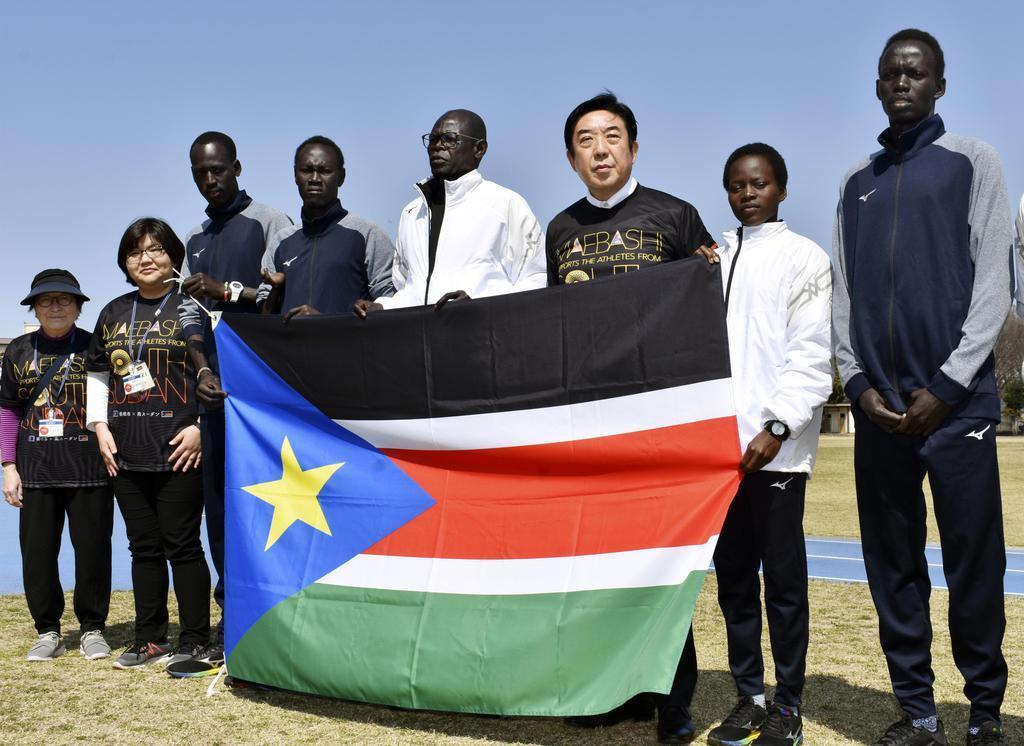南スーダンの国旗を手に選手たちと記念撮影する前橋市の山本龍市長(右から3人目)=26日午前、前橋市