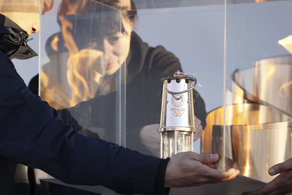 「復興の火」としての展示を終え、ランタンに納められる東京五輪の聖火=25日午後、福島県いわき市