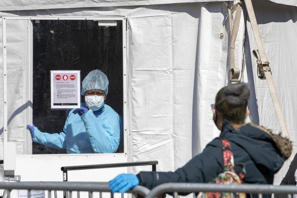 26日、米ニューヨークのブルックリン病院センターで、新型コロナウイルスの検査に並ぶ人への対応を行う医療従事者(AP)