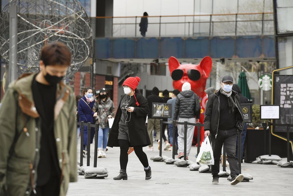 マスク姿の市民が行き交う北京市内の商業施設=26日(共同)