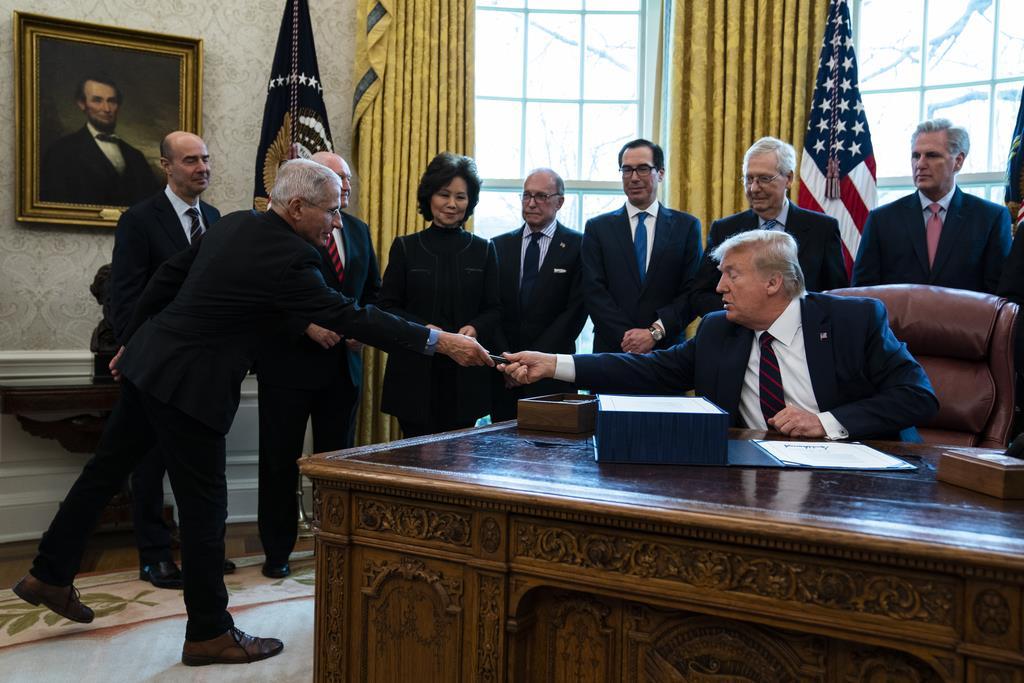 経済対策法案への署名後、国立アレルギー感染症研究所のファウチ所長にペンを渡すトランプ米大統領=27日、ホワイトハウス(AP)
