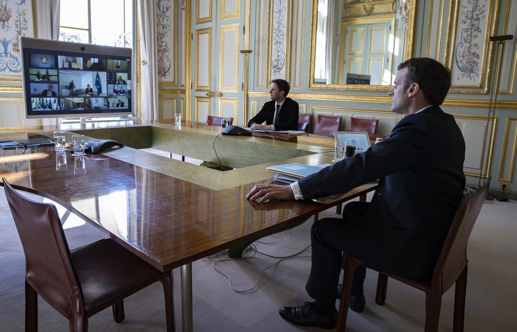 EU各国首脳とのテレビ会議に臨むフランスのマクロン大統領=26日、エリゼ宮(AP)