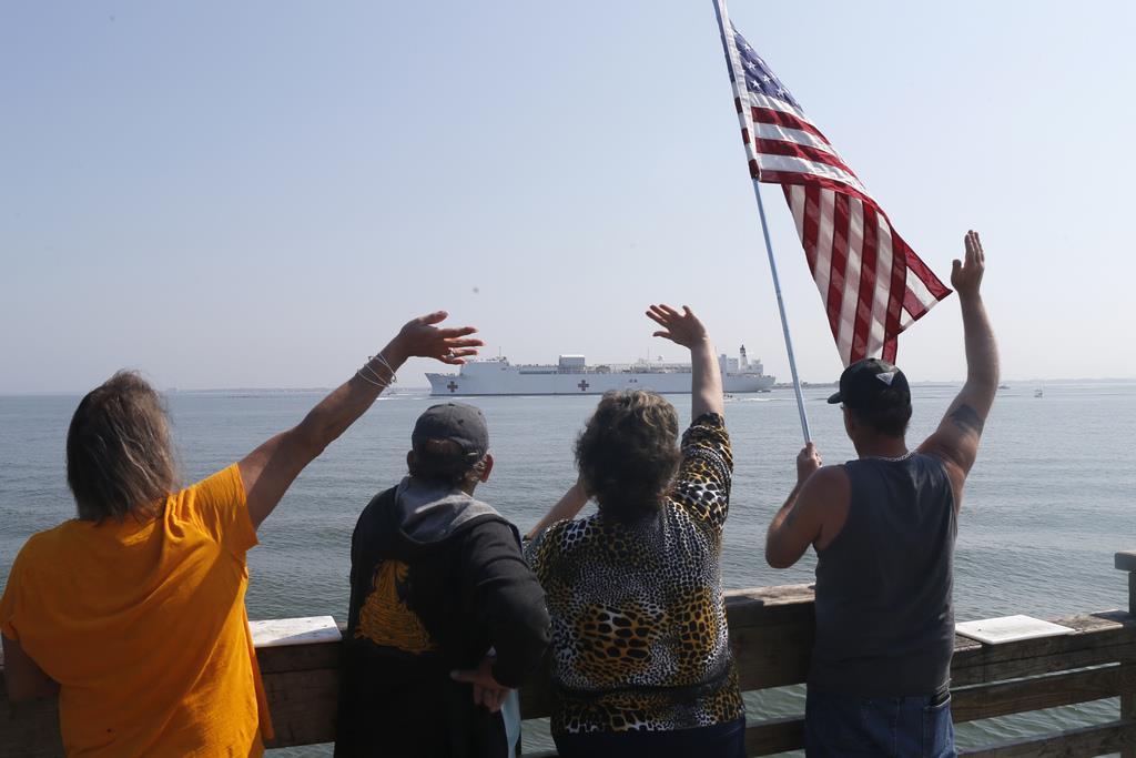 ニューヨークへ向かう病院船に国旗を掲げて手を振る人たち=28日、バージニア州ハンプトン(AP)