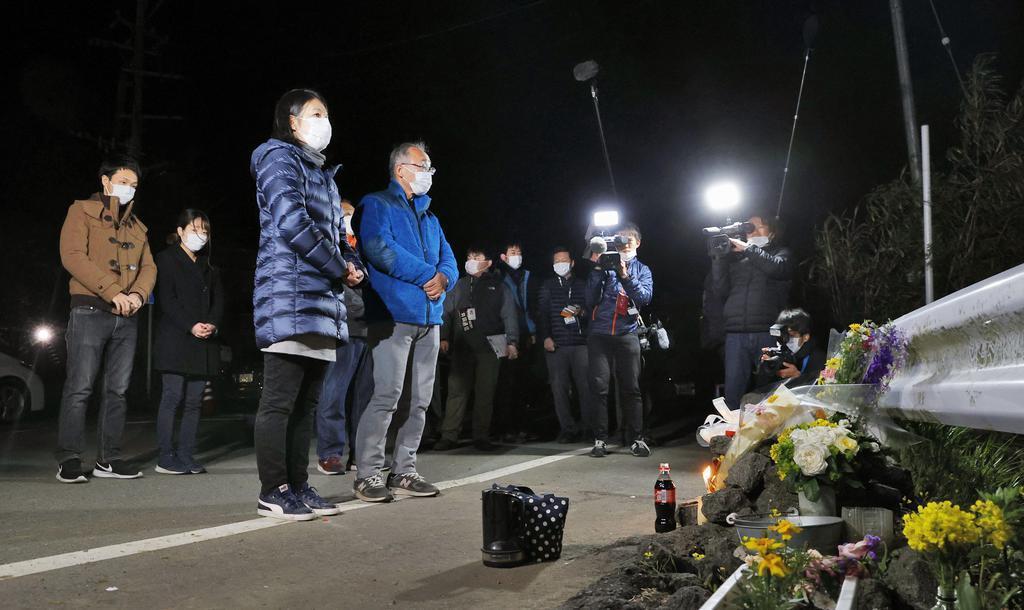 大和晃さんが犠牲になった阿蘇大橋の崩落現場付近を見つめる(左から)兄、翔吾さん、(1人おいて)母、忍さんと父、卓也さん=16日未明、熊本県南阿蘇村