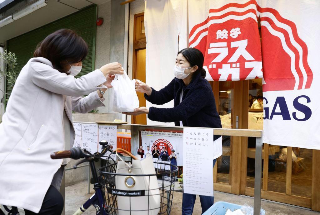 「テイクアウトFUKUOKA」で商品を受け取る女性=福岡市中央区