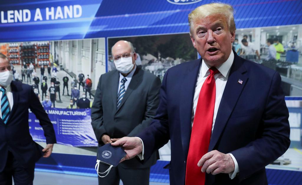 21日、米中西部ミシガン州の自動車工場で、マスクを手にしながら話すトランプ大統領(ロイター)