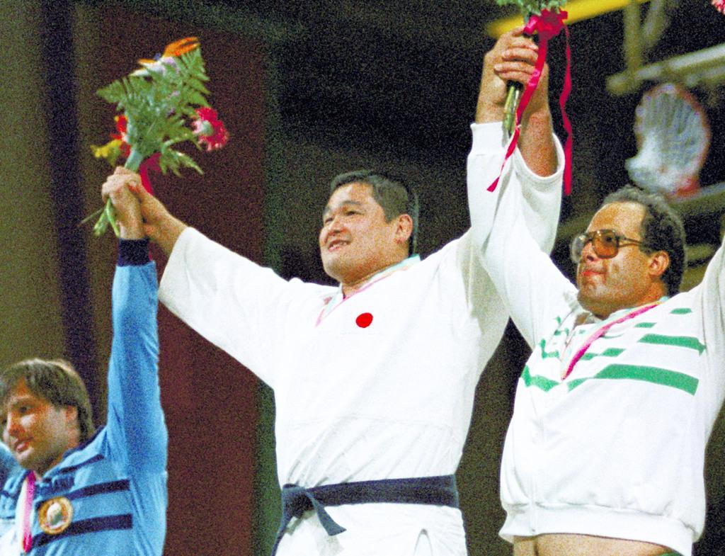 1984年8月、ロス五輪の柔道無差別級で金メダルを獲得し、表彰台で笑顔の山下泰裕さん。右は2位のラシュワン選手(共同)