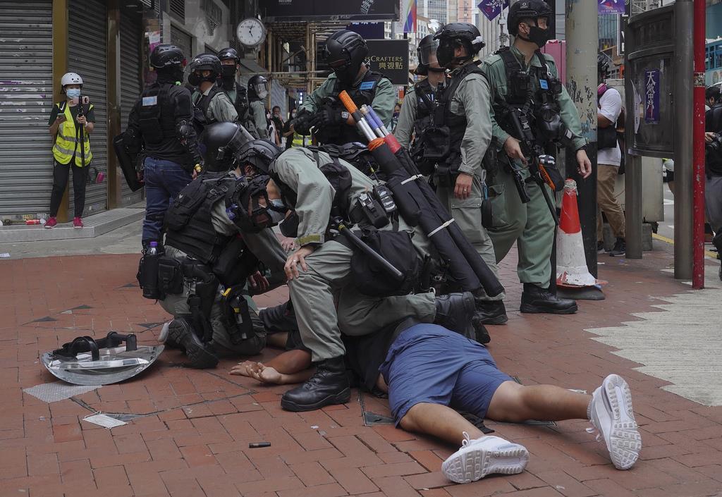 24日、国家安全法導入に反対して行われた香港のデモで、参加者を荒々しく取り押さえる警官隊(AP)