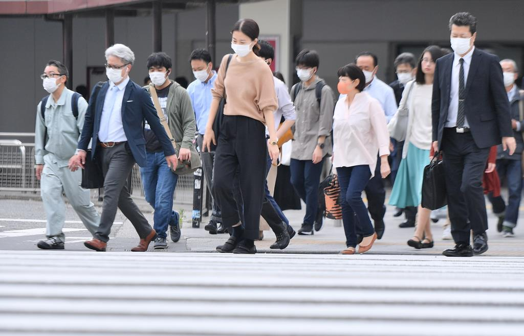 JR品川駅周辺で、マスク姿で職場に向かう人たち=26日午後、東京都港区(宮崎瑞穂撮影)