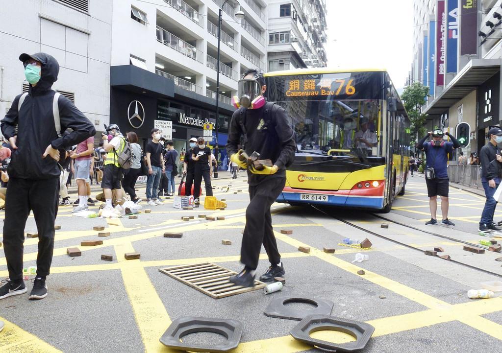 香港の繁華街コーズウェイベイ(銅鑼湾)で、れんがを運ぶデモ参加者(共同)