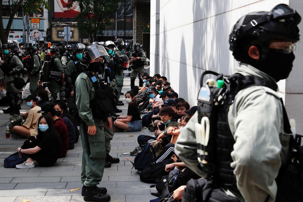 27日、香港で、警察に拘束され座らされるデモ参加者(ロイター=共同)