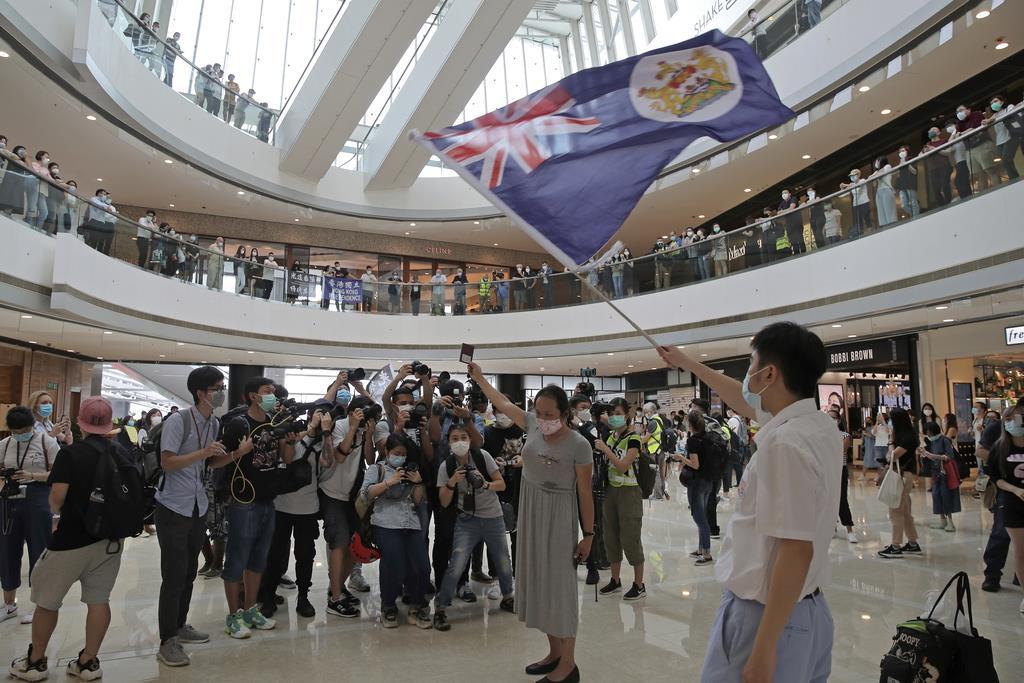 香港の商業施設で、英領香港時代の旗や「英国海外市民旅券」を掲げて国家安全法に抗議する市民ら=29日(AP)